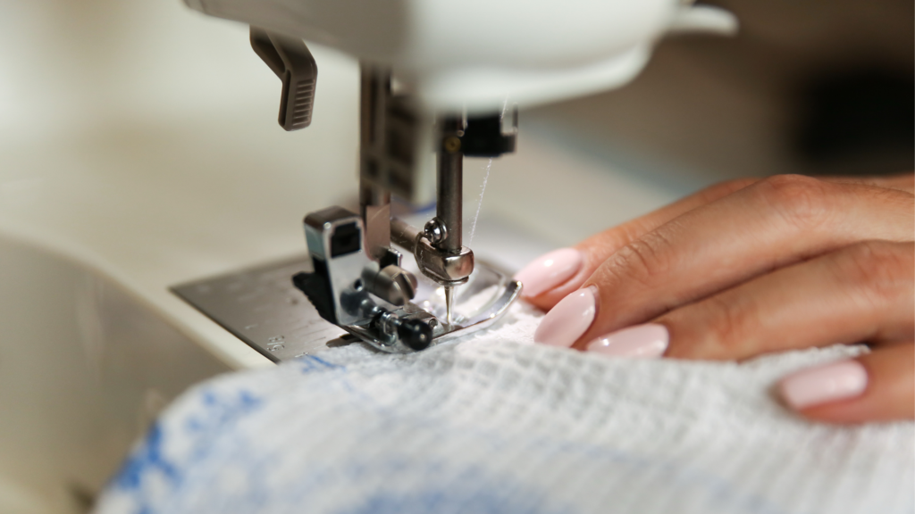 Somebody sewing a white fabric