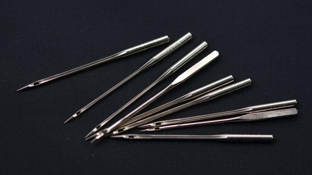 A bunch of sewing machine needles laying on a black fabric