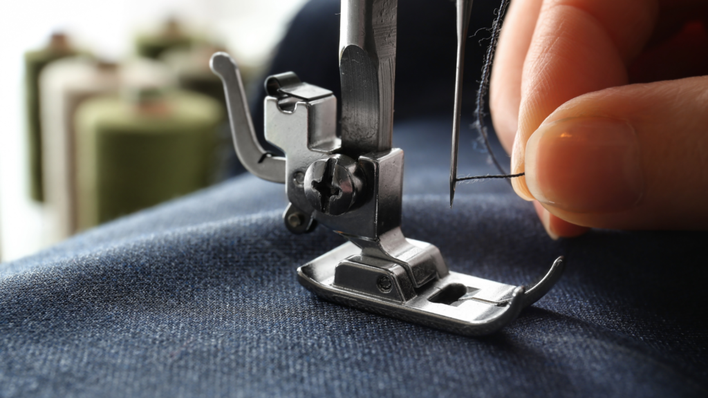 Close up photo of the sewing machine needle and thread being pulled by a pair of finger
