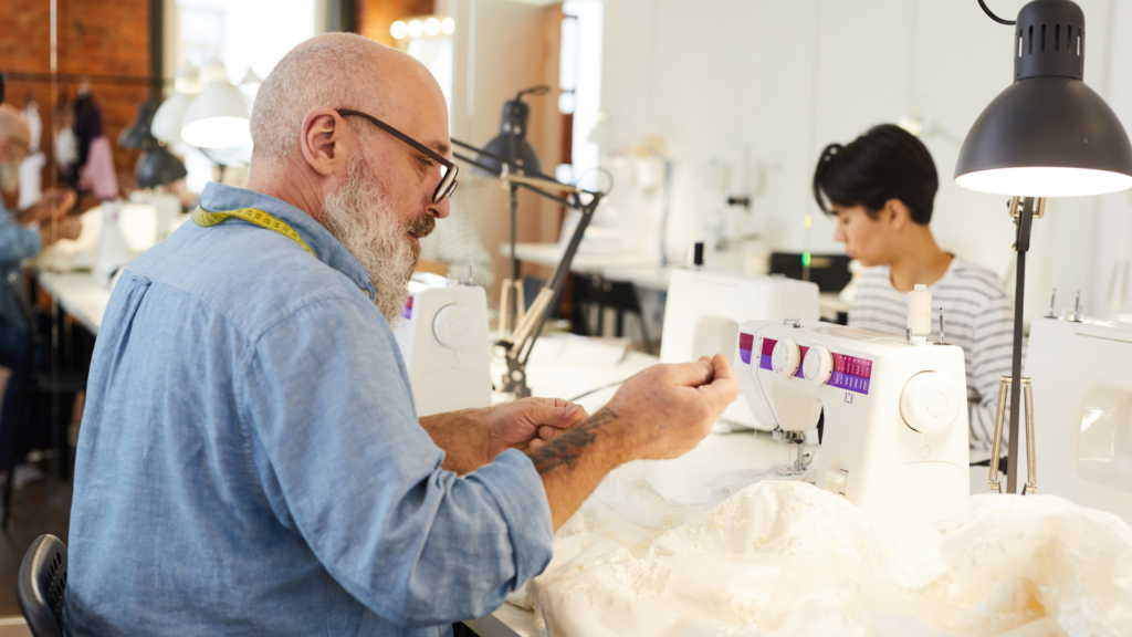 A man preparing to sew with a sewing machine