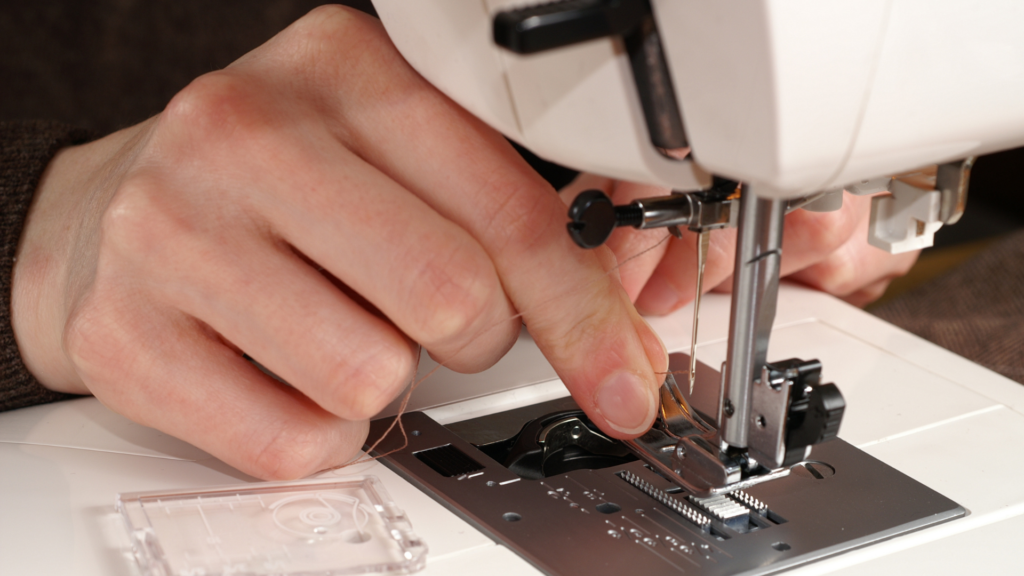 A person threading the sewing machine needle